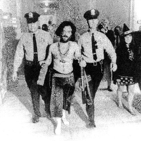 A grainy, black and white photograph of a shirtless man with dark hair being led down a hallway by two uniformed police officers