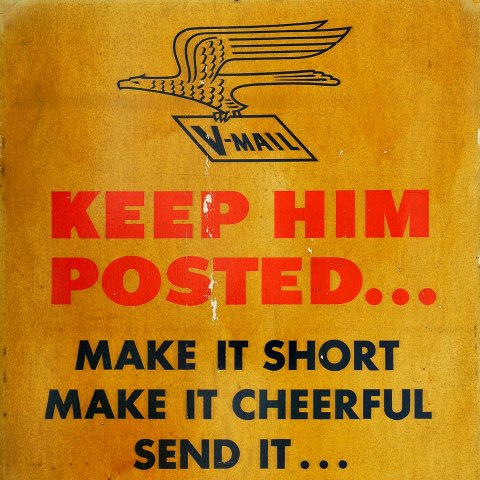 "golden sign with red and bold lettering and an eagle holding a paper that says ""V-MAIL"""