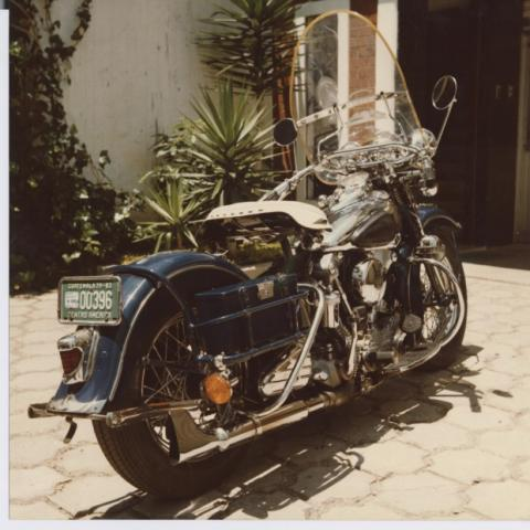 """On the right, the motorcycle parked in a driveway with a license plate that reads """"Guatemala 1979-1983."""""""