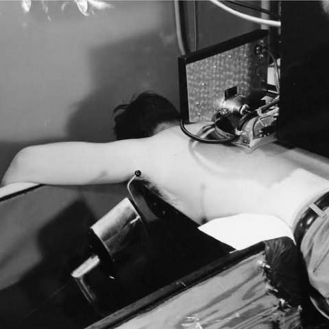 Black and white photo of man laying face-down on medical instrument