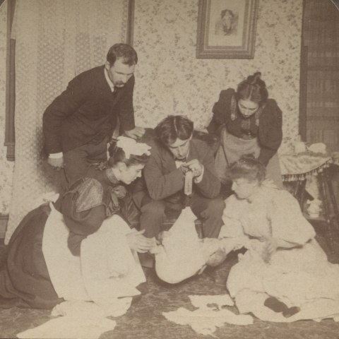 A double black and white image of a number of adults in a parlor surrounding an infant in a blanket. The central man is holding some sort of strap with a hook in his hands that is attached to the cloth the baby is lying in.