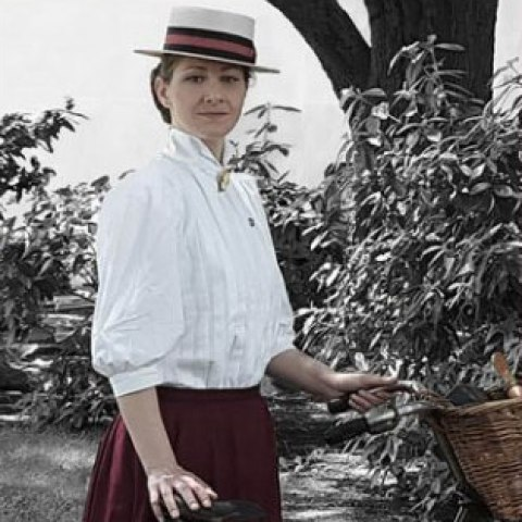 Photo of the actor playing Louise, standing next to her bicycle. Setting is outdoors with tree and bush in background.