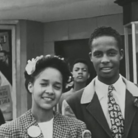 Still from a black and white movie. Movie poster in background. A young, nicely dressed African American woman and man stand together, smiling.