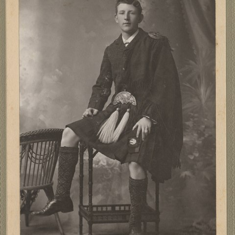 young man wearing a jacket and a kilt seated upon a desk or similar furniture