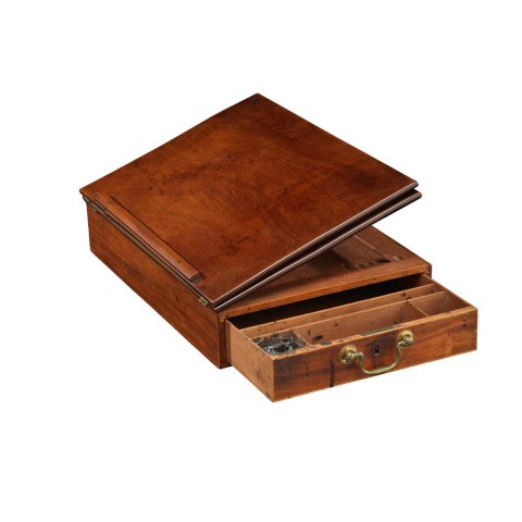 A portable desk. The desk's single drawer is partialy open, and its top is a raised position, tilted slightly in order to facilitate holding a piece of paper.