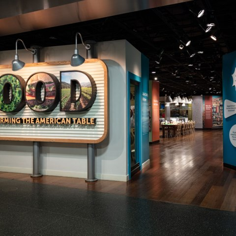 "Entrance to exhibit with large sign that says ""FOOD"" with pictures of various foods in each letter."