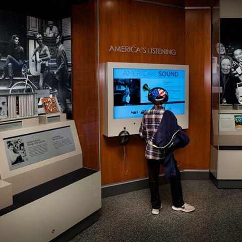 Display cases with boy standing at interactive station