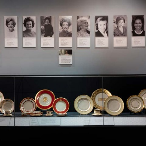 White House china displayed beneath First Ladies portraits