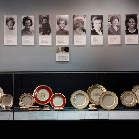 White House china displayed beneath First Ladies portraits