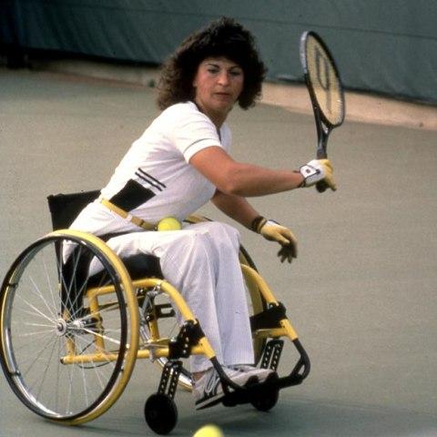 Woman in wheelchair hitting a tennis ball