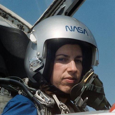 Woman wearing helmet in aircraft cockpit