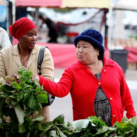 two women look through a farmers market