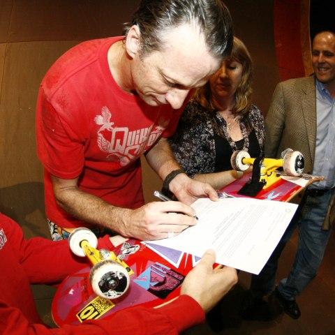 Tony Hawk signs deed of giftfor his skatedeck, photo by Lee Leal, Embassy Skateboards