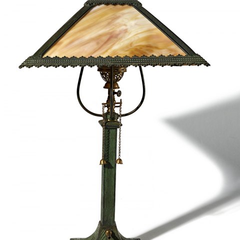 A dark colored lamp with a tan shade