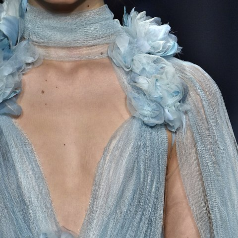 A closeup of a model's chest and shoulder. She wears a filmy periwinkle gown with fabric roses sewn on.