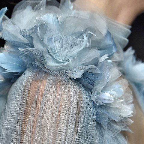 A closeup of a model's shoulder. She wears a filmy periwinkle gown with fabric roses sewn on.