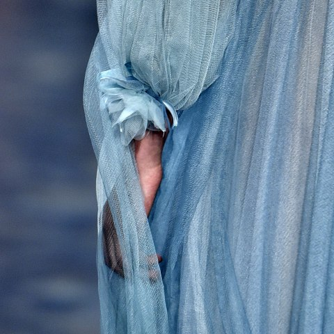 A closeup of the arm of a model wearing a periwinkle-colored blue filmy gown with long sleeves and a rose at the wrist