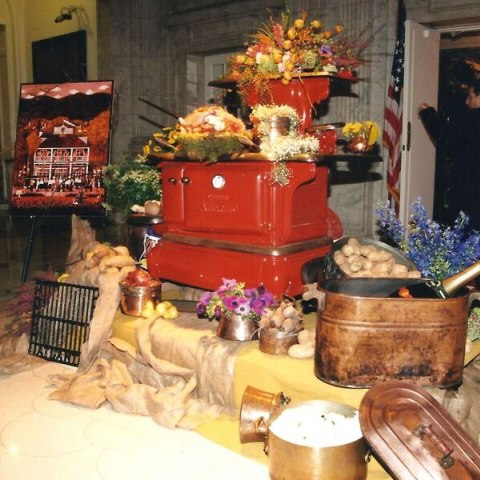A small red metal stove is surrounded by objects that are also heaped on it