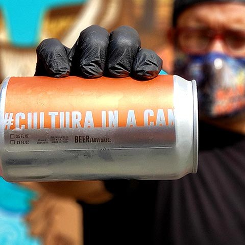 Man holding can with words, cultura in a can