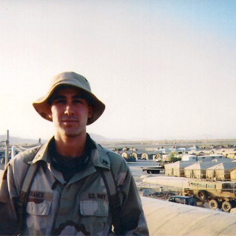 Young man in army uniform with a desert military base in background