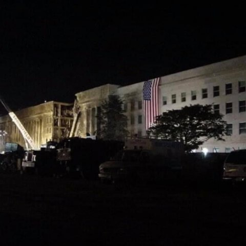 Pentagon at night with fallen wall, American flag, and crane