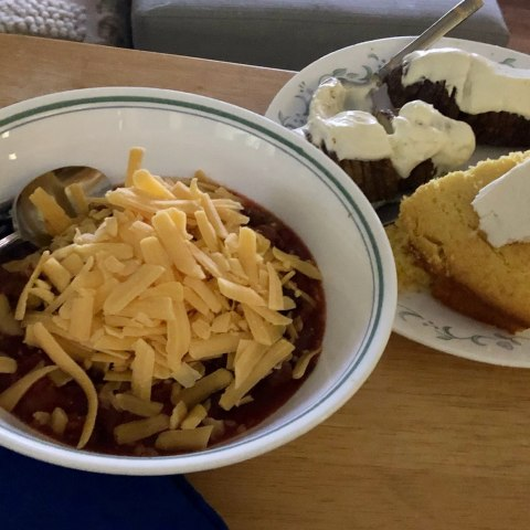 Bowl of chili topped with grated cheese and plate with slice of cornbread and chocolate cake