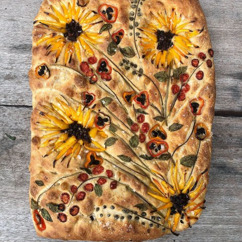 Baked Focaccia bread in which vegetables look like flowers on the surface
