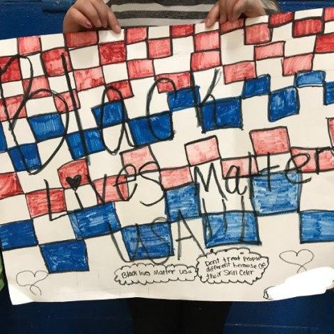 Several children's hands hold a handmade sign for Black Lives Matter