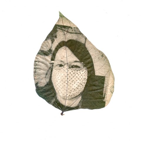 Black and white art photograph printed on leaf of woman wearing mask over her mouth and chin