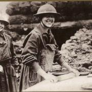 "This 1918 photo from the National Archives shows a cheerful American Salvation Army ""lassy"" rolling pie crusts for men of the 26th Division in France."