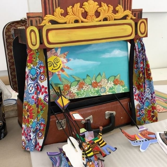 Open suitcase with paper puppets