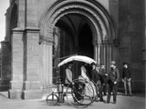 This photo shows the Copeland steam-propelled tricycle in front of the Carriage Porch at the north entrance Smithsonian Institution Building (the Castle) on the Mall.
