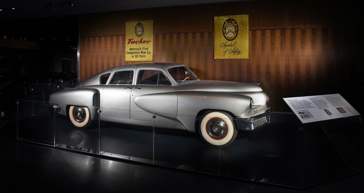 A silver Tucker sedan (a car with pronounced curves), against a wood paneled wall.