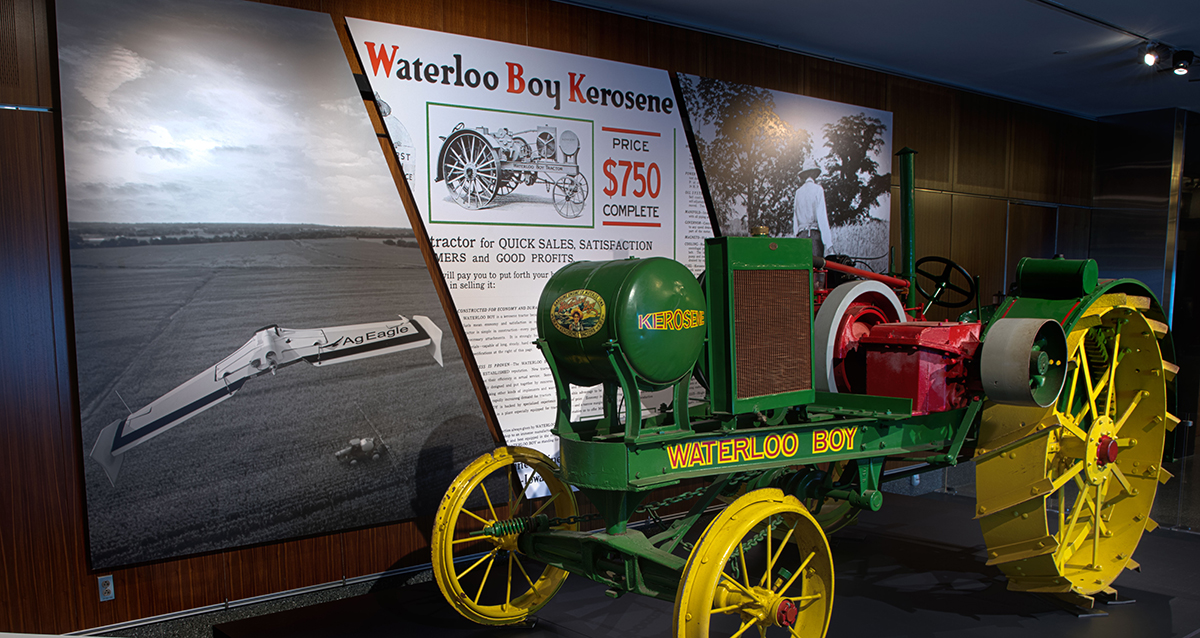 A photograph of a green tractor with yellow wheels. In the background are large photographs of a drone and advertisements for the Waterloo Boy tractor.